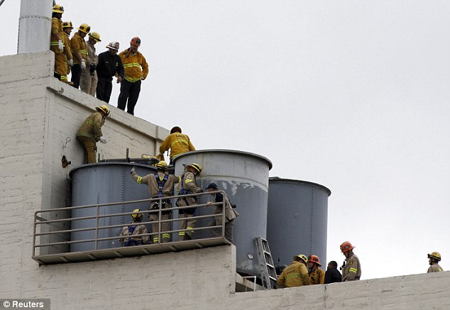 Mystery: Los Angeles fire fighters peer down at the water tanks on the roof of the Hotel Cecil as they try to figure out how to remove the body of a young woman found inside