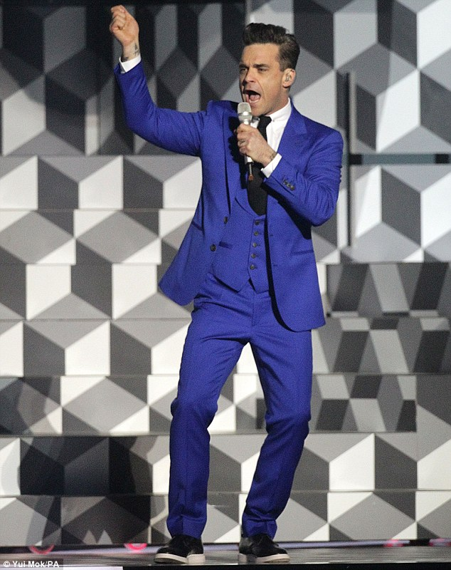 Dapper: The singer wore a three-piece blue suit as he performed on stage