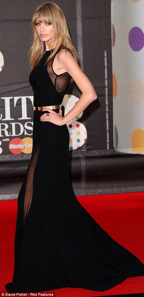 Similar styles: Taylor Swift also opted for a similar dress to Jessie - highlighting her trim waist with a gold belt around her black gown