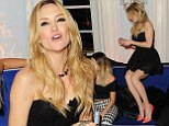 Having fun? Kate Hudson kicks up her heels as she dances on the sofa at Warner's Brit Awards after-party