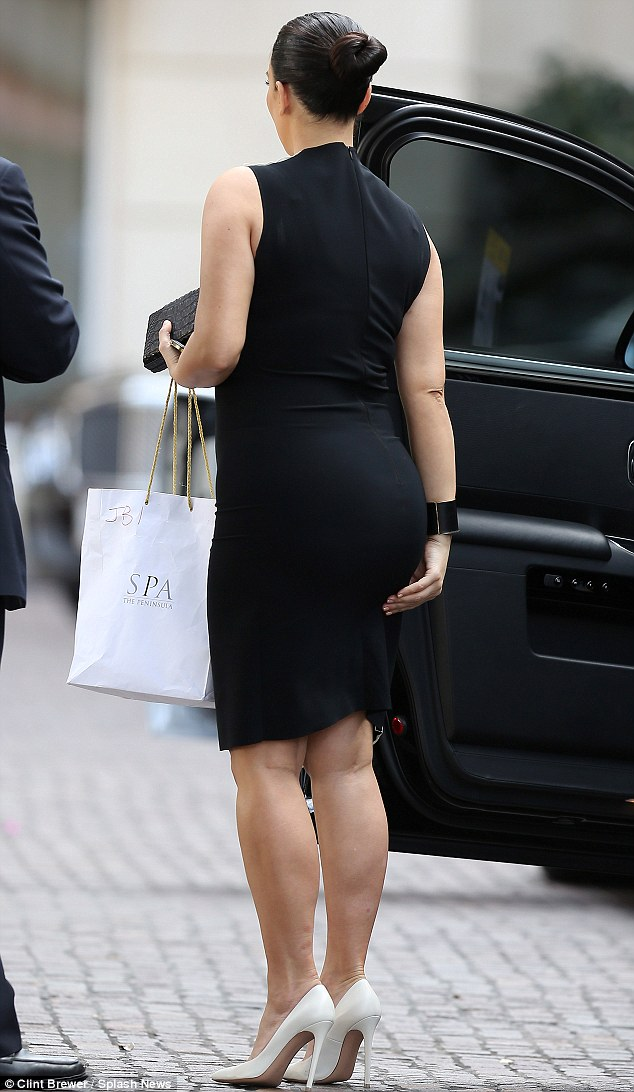Keeping in check: As she exited her car at her destination, Kim made sure to smooth down her dress