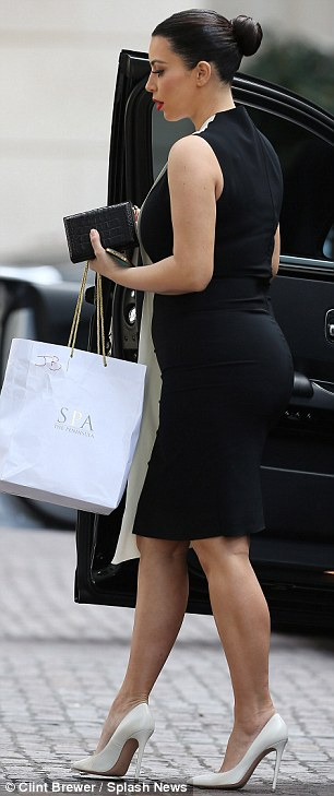Spliced: The pregnant 32-year-old wore a black and white spliced ensemble, which showed plenty of her curves at the back on onside but disguised them on the other