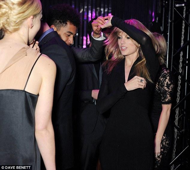 Hitting the dancefloor: Carey looks on as Taylor dances with Jordan Stephens of the Rizzle Kicks