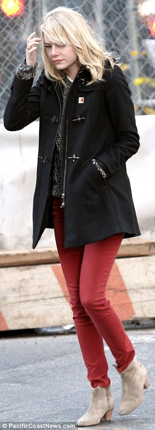 On the go: Emma kept her hands in her jacket pocket as she wore a knitted jumper with a pair of red jeans and camel coloured boots