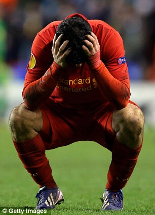 Contrast: Suarez holds his head in his hands after Liverpool went out of the Eurpopa League on away goals
