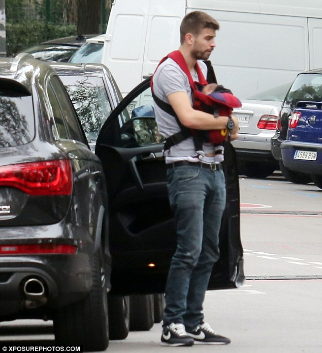 Doting daddy: Gerard Piqué was seen holding his son Milan in a baby carrier as he followed Shakira's lead out of restaurant Real Club de Tenis Barcelona