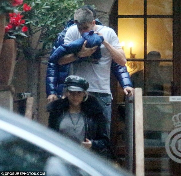 Cute: Gerard showered Milan with a number of kisses as held as he made his way to the couple's car