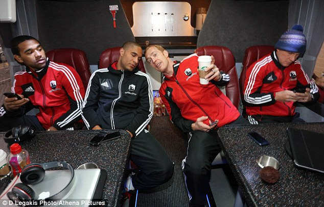 Long trip, Ashley? Swansea captain Williams has a snooze as Gerhard Tremmel toasts him with a coffee
