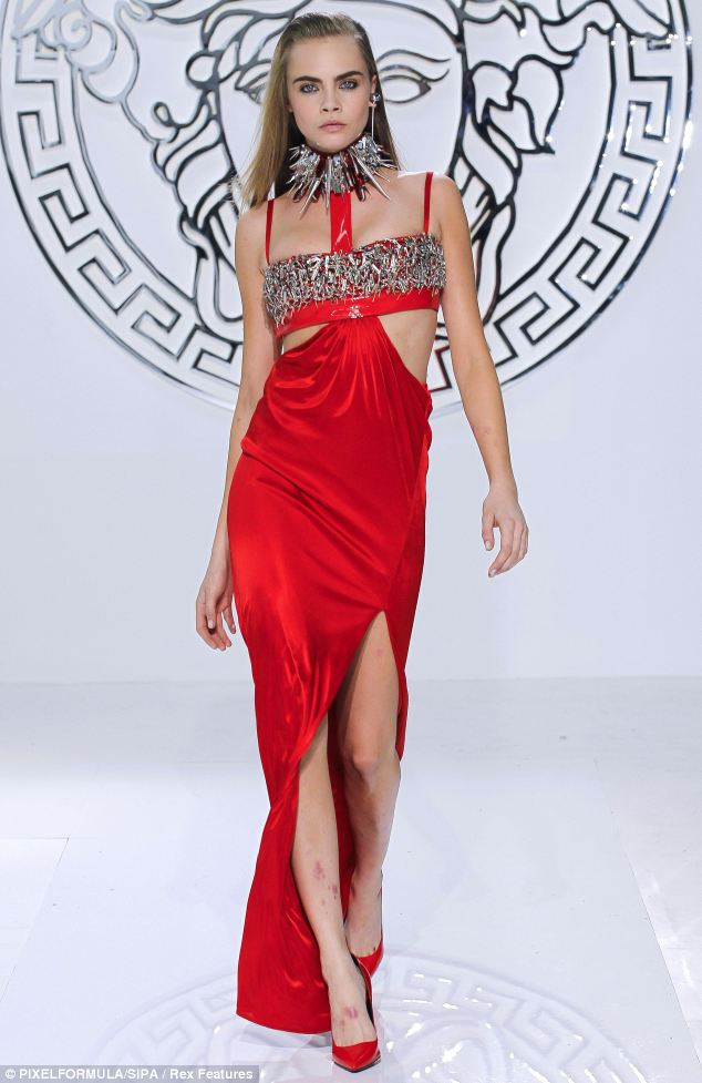 The thigh-high split in the red Versace gown revealed angry red blemishes on the legs of 20-year-old Cara Delevingne