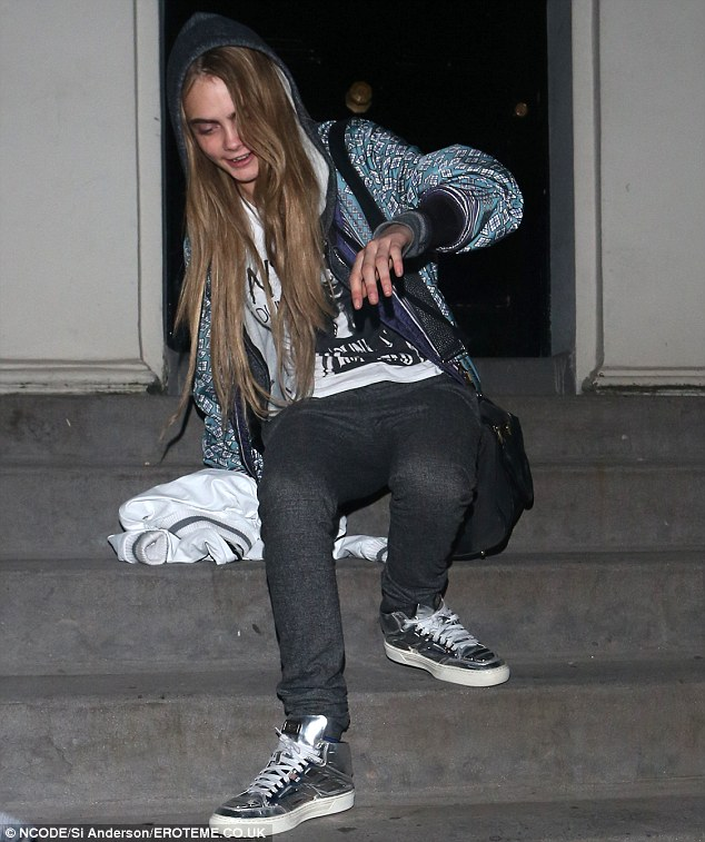 Party girl: Cara Delevingne is pictured falling down the stairs while leaving a house party in London