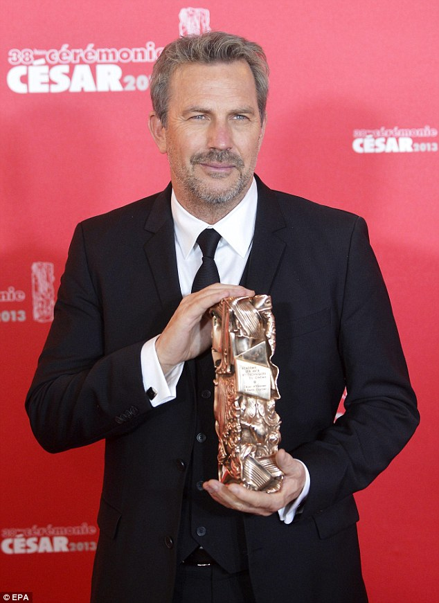 Take a bow: Kevin Costner holds his Cesar of Honor as he poses for photographs in the press room