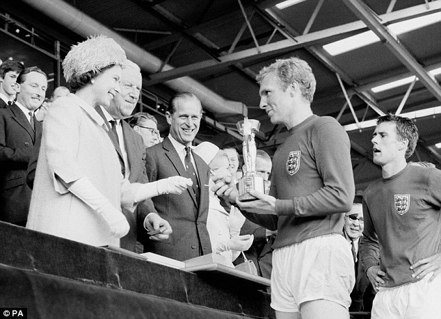 Finest hour: Bobby Moore collects the Jules Rimet trophy from the Queen at Wembley in 1966