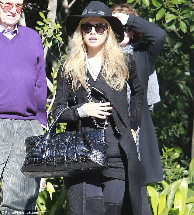 Back to black: Rachel sported an entirely black ensemble for the bash, including a wide brimmed hat to protect her pale skin from the sun