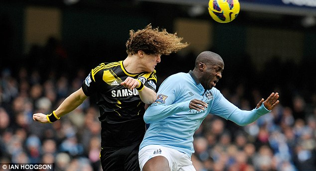 High jump: Chelsea defender David Luiz wins an aerial battle with Yaya Toure