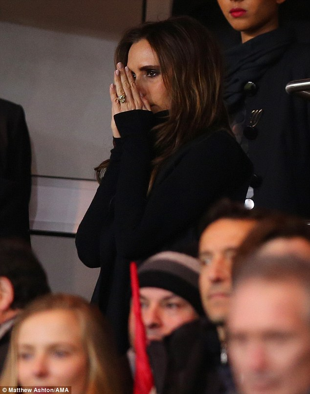 Nervous Victoria? The concerned looking spice Girls star seemed to pray as she took her seat ready to watch husband David make his debut for his new Paris football team on Sunday night