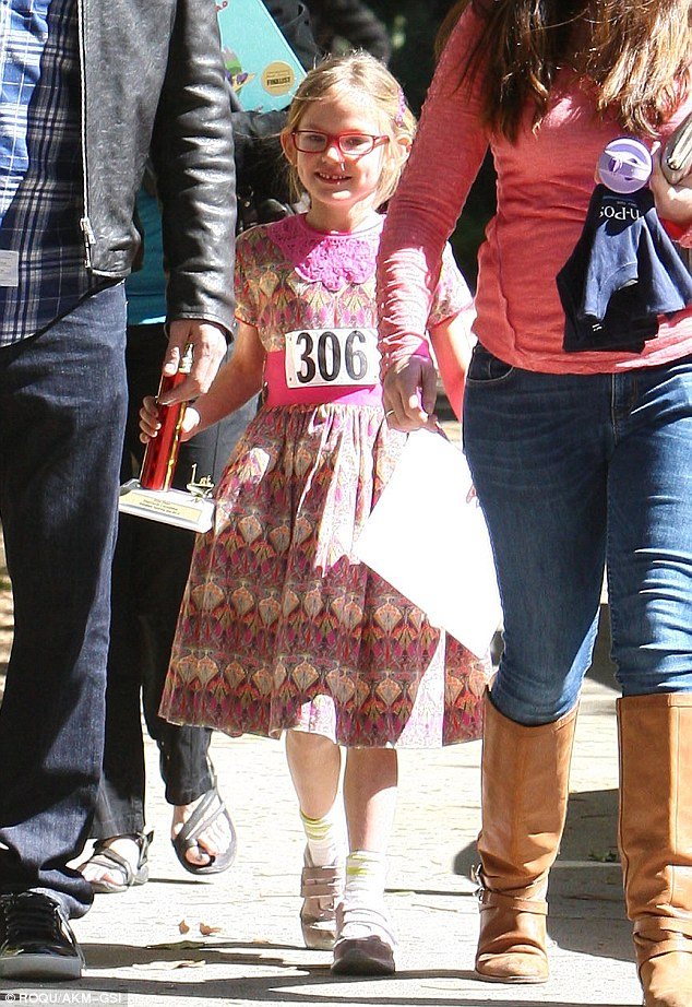 The victor: Violet clutched her spelling bee award and still wore her competition number on front of her dress