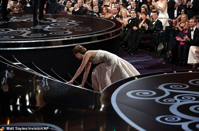 """Jennifer Lawrence falls as she approaches the stage to accept her award for best actress for """"Silver Linings Playbook"""