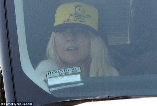 Fresh-faced: The singer was clearly make-up free as she hid behind a hat