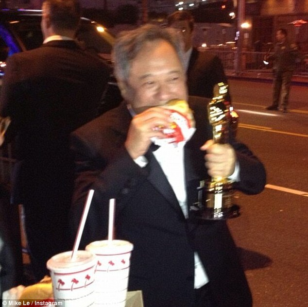 Not to be outdone: Ang Lee held his best director Oscar in one hand and ate an In-N-Out Burger with the other after the four-hour event
