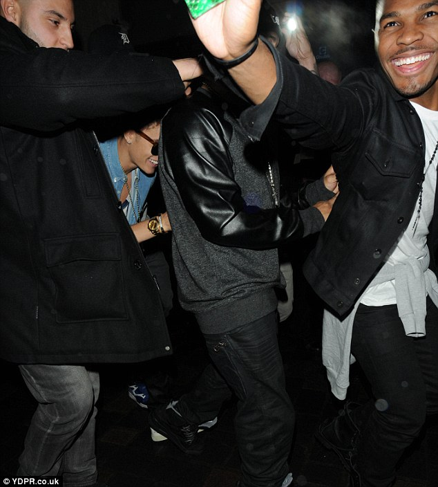 We can see you! Justin grinned to himself as he attempted to hide among his entourage while the group headed back from London's Cirque du Soir nightclub after an evening out