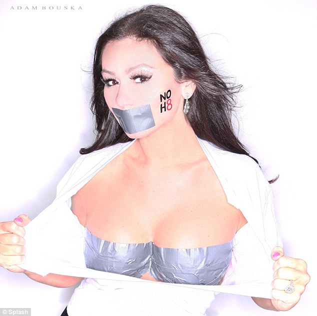 Exposed: Slipping on a white shirt, the 26-year-old reality star rips open the attire to reveal her taped cleavage