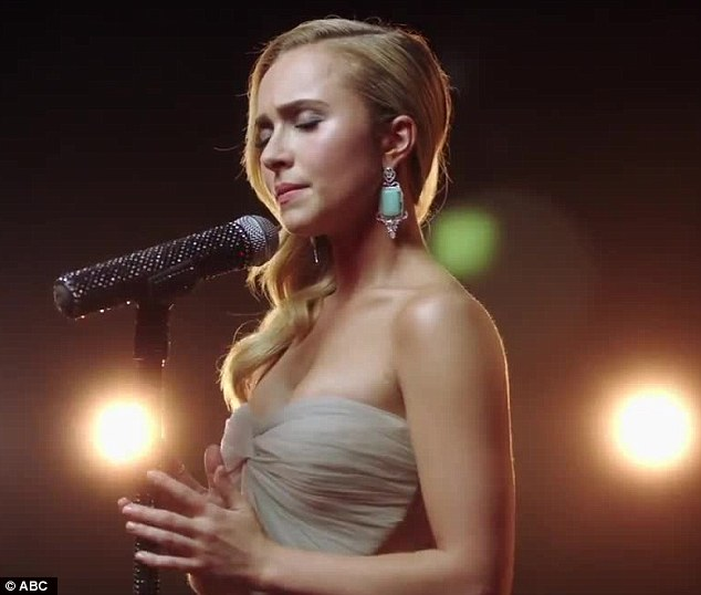 Belting out a tune: The 23-year-old belts out the 1980's hit song Fame as she stands onstage in an empty auditorium wearing a dramatic strapless sheer gown