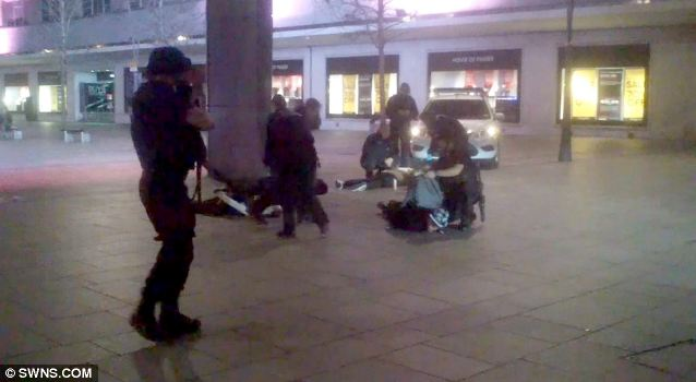 Careful: An armed officer keeps guard with his weapon as police search the gang on the floor