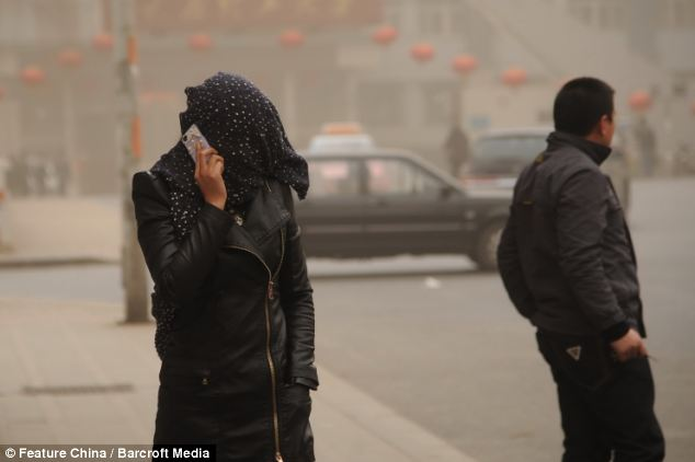 Sandstorm: A woman covers her face with a scarf during in Taiyuan to try and protect herself from the air