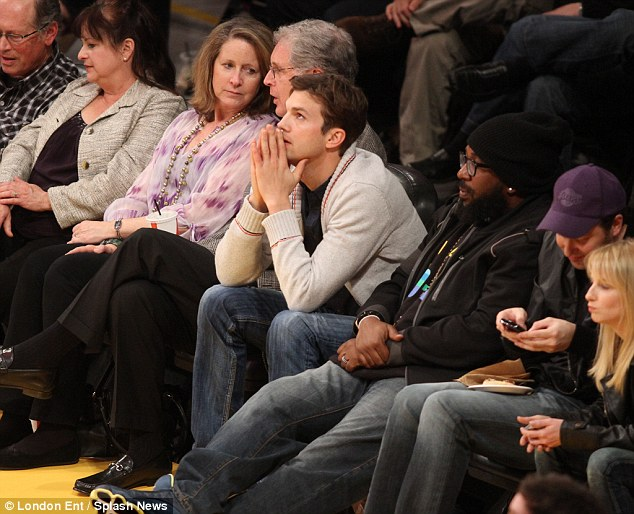 All alone? Ashton Kutcher sits courtside on his own at the Lakers game in LA on Thursday, while girlfriend Mila Kunis is in London