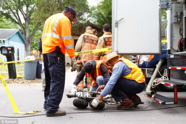 Recovery effort: Crews deploy a cable controlled robot into a storm drain to look for additional damage