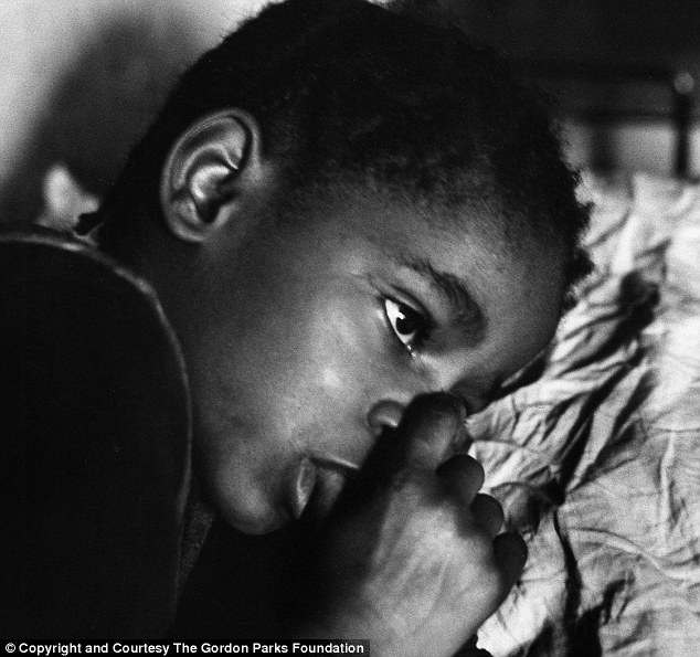Growing up with nothing: One of the Fontenelle children tries to sleep in their home. The children couldn't go to school because of their lack of winter clothes
