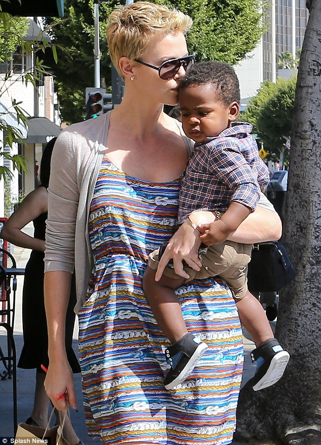 Star in stripes: Charlize Theron cuddles up to her little son Jackson after taking him for a haircut in Beverly Hills on Saturday