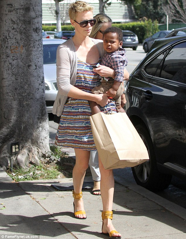 Cuddles: Charlize was back in mom mode after glamming up for the Oscars last weekend