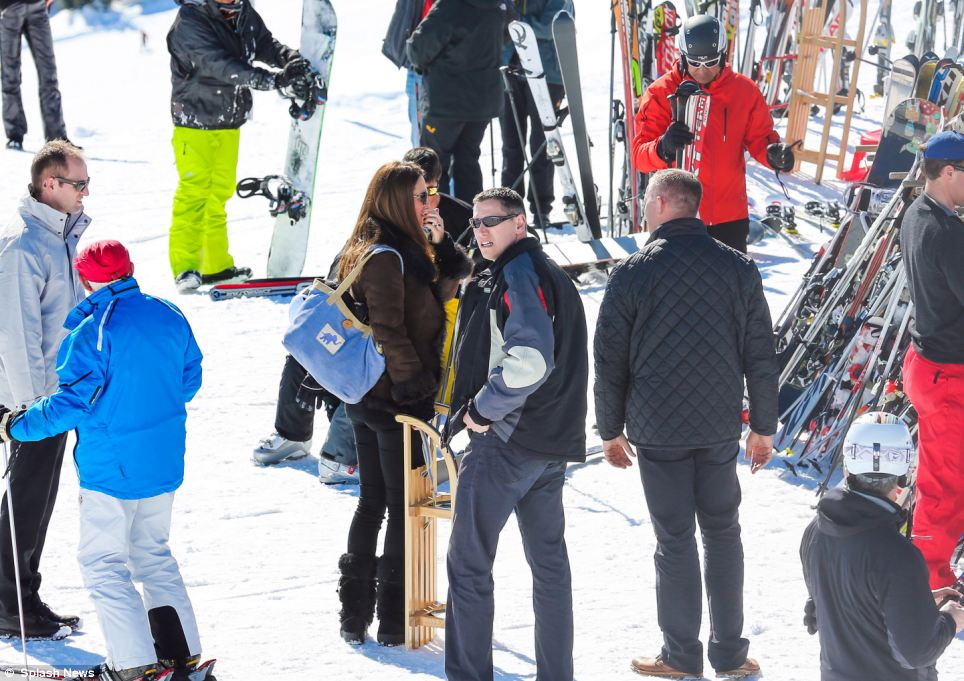 On the slopes: Dressed in black trousers and boots and shades, Kate chats to friends at the luxury resort