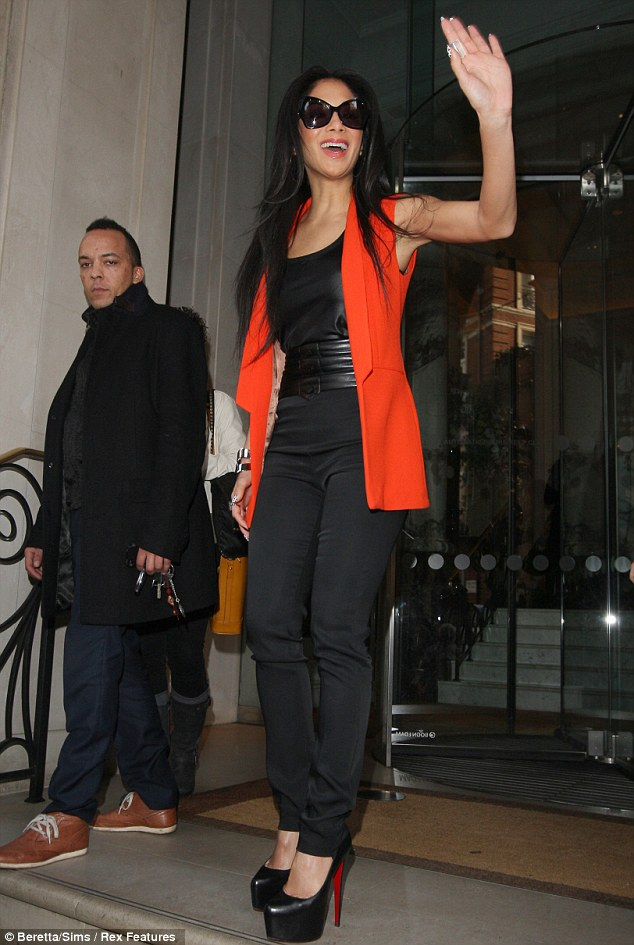 Saying hello: Scherzinger beamed as she waved to fans who had gathered outside the hotel