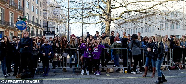 They've forgiven him! Dozens of 'Beliebers' wait outside Justin's London hotel on Tuesday for a glimpse of their idol
