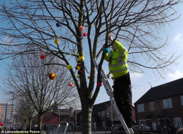 Woolly thinking? Leicestershire Police officers hang knitted pom poms from a tree to try and reduce the fear of crime