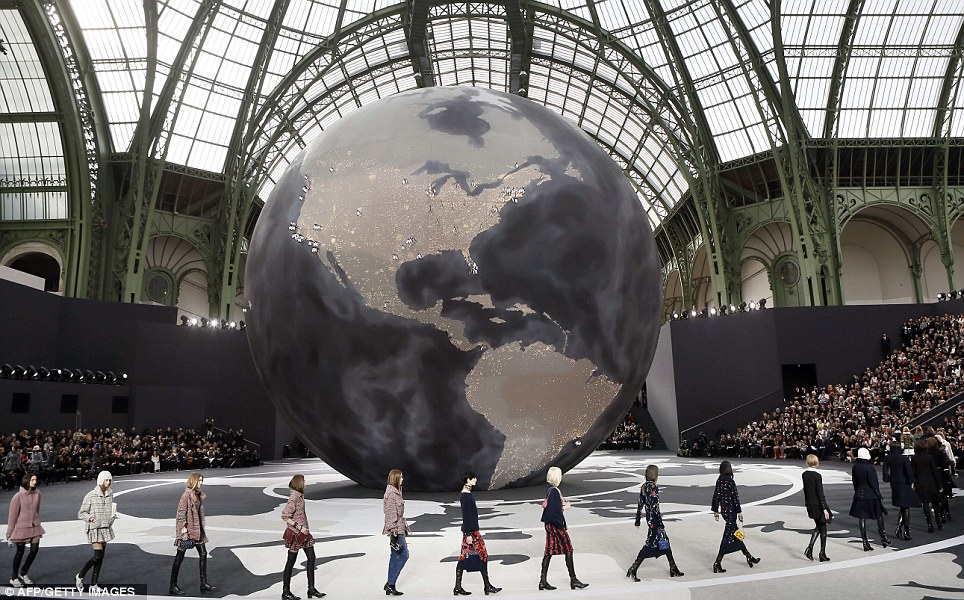 Out of this world: The models orbited a globe in the middle of the stage under the glass roof of the Grand Palais exhibition hall