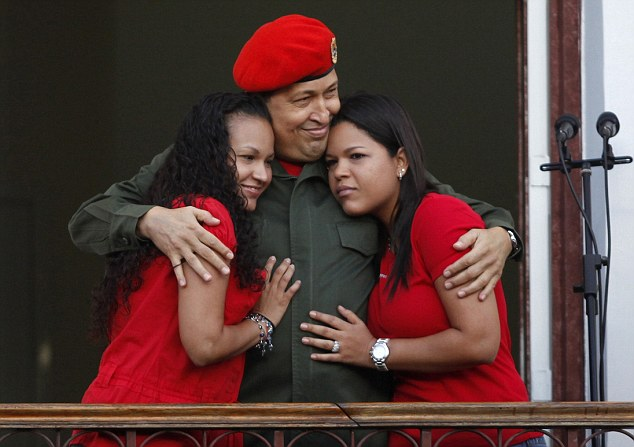 Family: Venezuela's President Hugo Chavez hugs his daughters Rosa (left) and Maria (right) while appearing to supporters on a balcony of Miraflores Palace soon after his return to the country from Cuba in July 2011