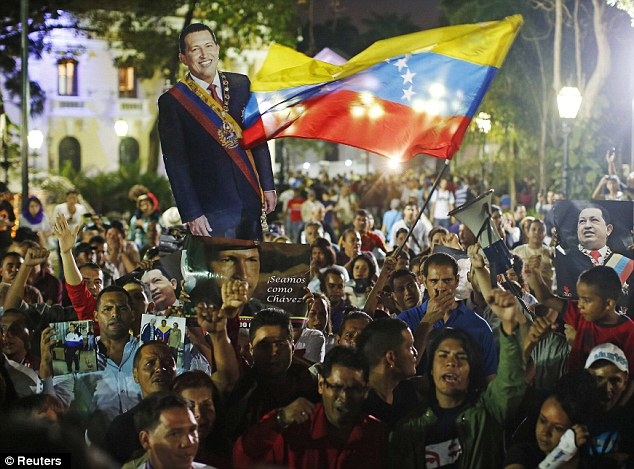 Crowds: Supporters gather in Caracas after the announcement, waving the national flag and carrying a cutout of the President