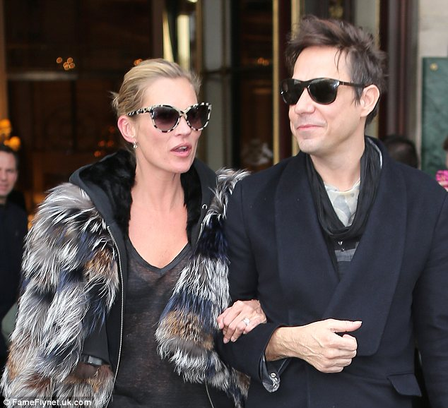 Escorted by my man: Kate was led out of Le Meurice hotel by husband Jamie Hince and the pair seemed in good spirits
