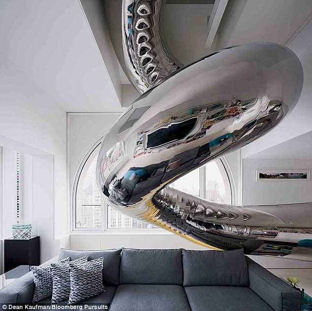 Slide: The young-at-heart owners have installed a four-story mirror polished stainless steel slide, pictured, in their apartment so they can twist and turn their way around the stunning home