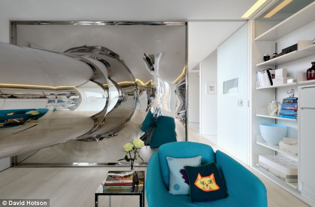 As the shiny slide reaches the end, the material flares out to create a distorted rectangular mirror