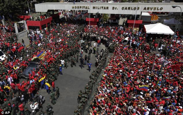 Start of procession: The flag-draped coffin containing the body of Venezuela's late President Hugo Chavez, left, is taken from the hospital where he died