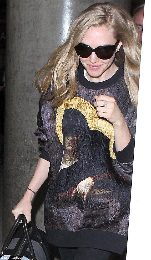 So artsy: Amanda Seyfried donned a portrait print sweater as she arrived in Los Angeles on Wednesday