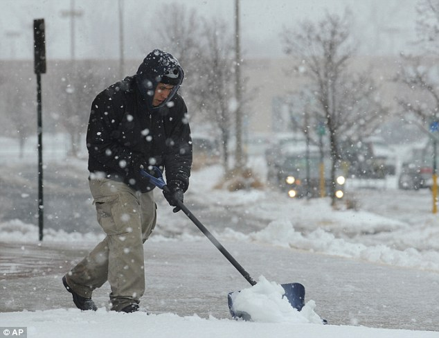 Shoveling: Enrique Gomez clears the sidewalk in front of Starbucks in the Stafford Marketplace shopping center along Garrisonville Road as the first significant snowfall of the season hits Stafford County, Va.