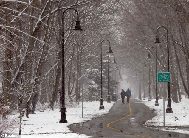 Dusting: Pedestrians walk through the snow at the beginning of a winter storm in Somerville, Massachusetts