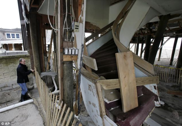 Destroyed: Scott Clayton, of Bay Head, stops by his family's Superstorm Sandy damaged home in Mantoloking, New Jersey, to check on new storm damage on Thursday