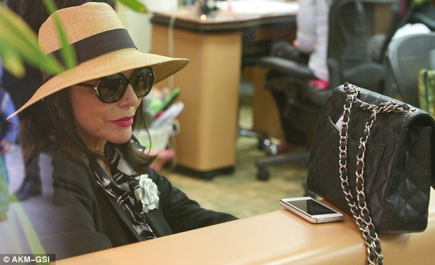 Chic: Red lips and oversized sunglasses, Joan looks every bit the A-lister