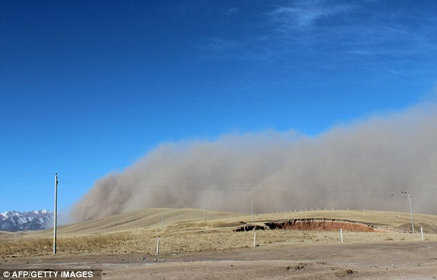 Phenomenon: The rolling wall of dust and sand is seen sweeping the landscape beneath a blue sky in China